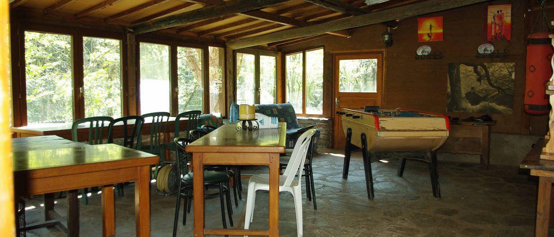 salle commune terrasse couverte du gite de Roubigiès, baby-foot, tables et chaises de réception pour groupes