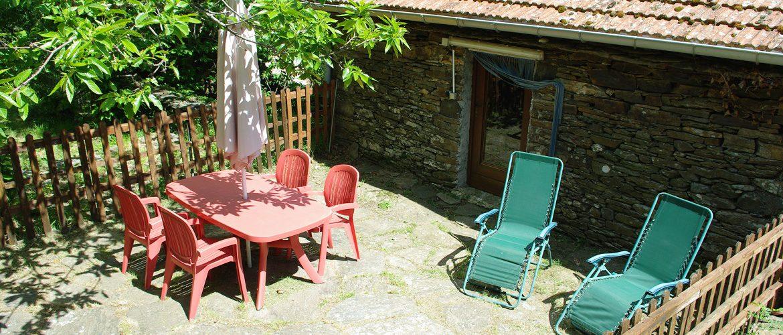 vue de la terrasse du gite de la clède, salon de jardin transat et lauzes au sol.